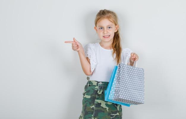 Meisje wijst naar kant met papieren zakken in wit t-shirt