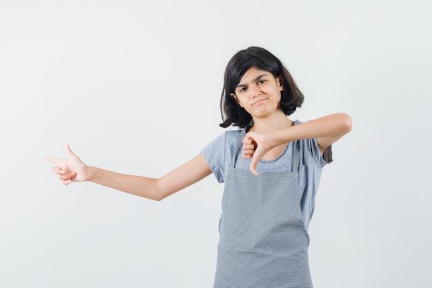 Meisje wijst opzij, toont duim in t-shirt, schort en kijkt teleurgesteld, vooraanzicht.