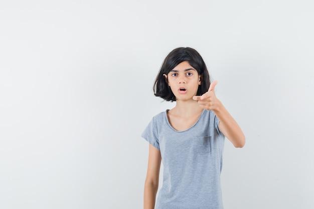 Meisje wijzend op camera in t-shirt en verbaasd op zoek. vooraanzicht.