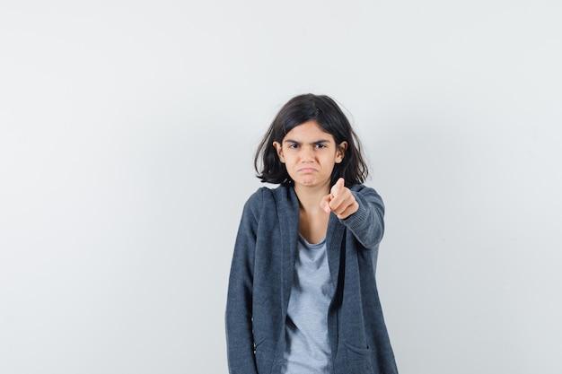 Meisje wijzend op camera in t-shirt, jasje en kijkt beledigd. vooraanzicht.