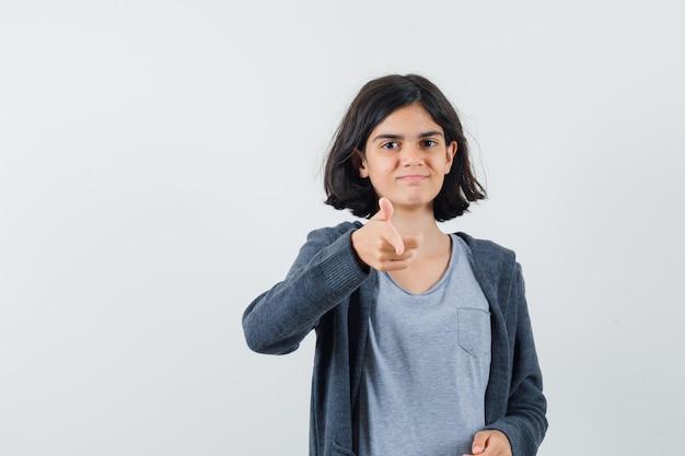 Meisje wijzend op camera in t-shirt, jasje en op zoek naar zelfverzekerd, vooraanzicht.