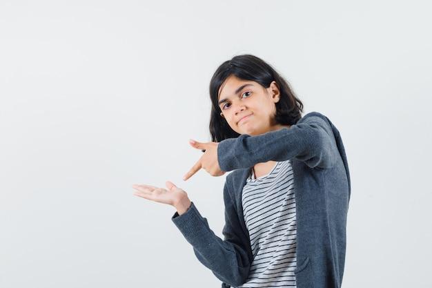 Meisje wijzend op haar lege handpalm in t-shirt, jasje en op zoek zelfverzekerd