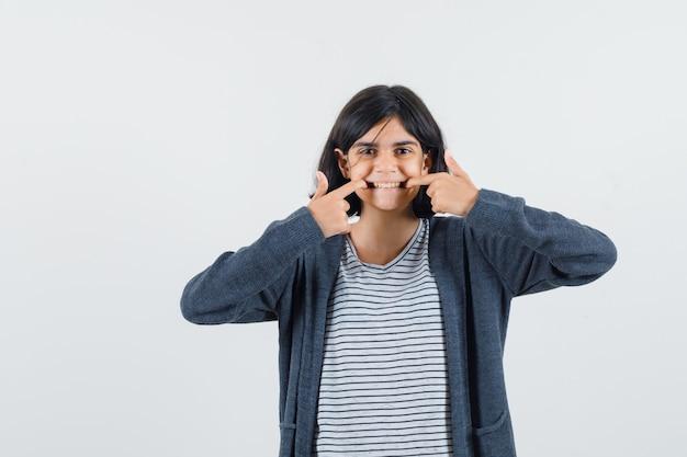 Meisje wijzend op haar tanden in t-shirt, jasje en op zoek zelfverzekerd