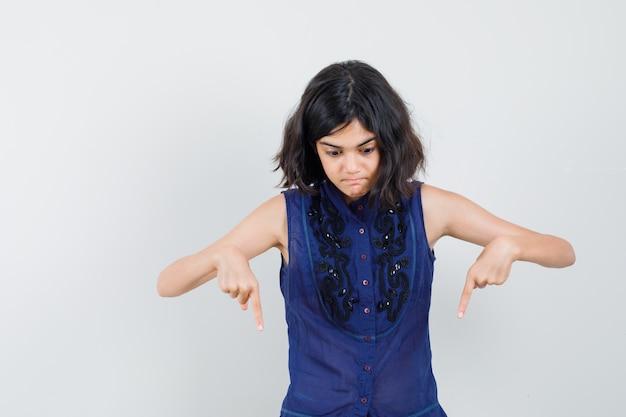 Meisje wijzende vingers naar beneden in blauwe blouse en op zoek geschokt