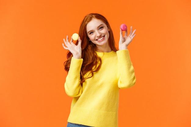 Meisje wil dessert delen, twee macarons houden en glimlachen