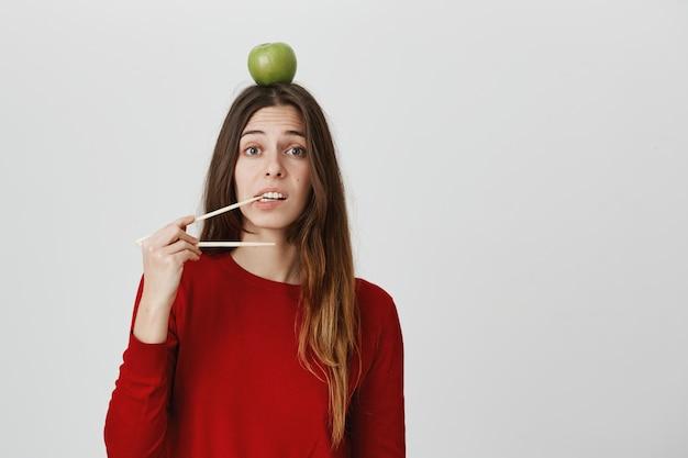 Meisje wil eten, eetstokjes bijten, groene appel op het hoofd houden