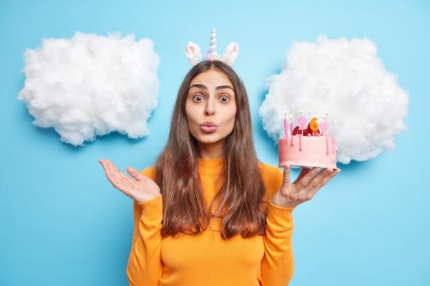 Meisje wil je kussen zegt bedankt voor felicitatie houdt heerlijke verjaardagstaart gekleed in vrijetijdskleding poses op blauw