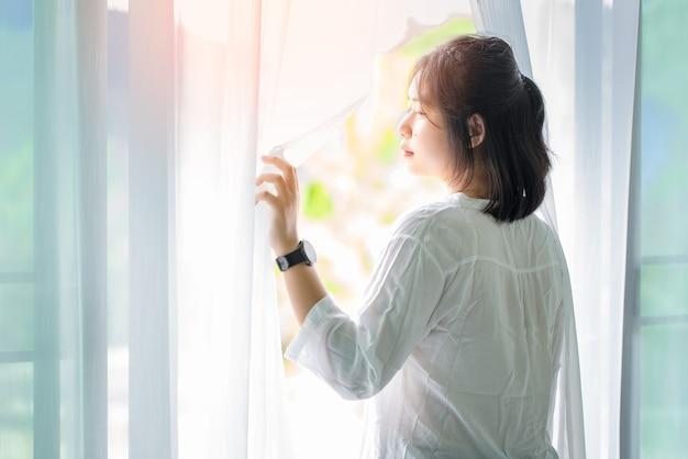 Meisje, word wakker en open de gordijnen in de ochtend om frisse lucht te krijgen.