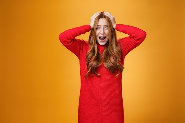 Meisje wordt gek van onder druk staande paniek, zich gespannen voelen en moeite hebben met schreeuwen van angst, maakt zich zorgen dat ze in een moeilijke situatie zit, hand in hand op het hoofd springende ogen, bezorgd poserend over oranje muur