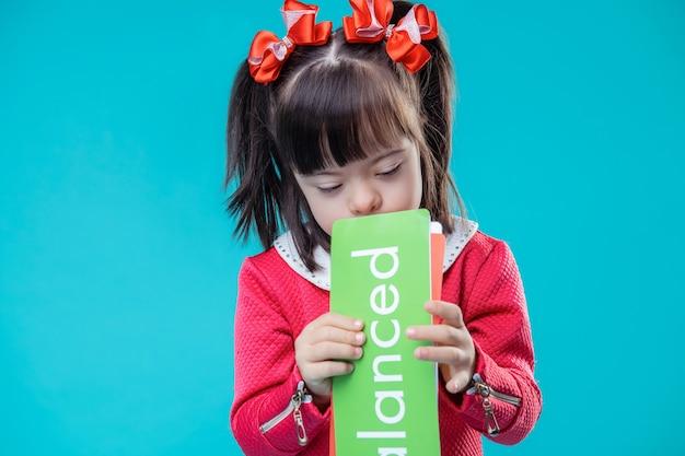 Meisje wordt geschokt. aanbiddelijk jong geitje in helemaal rode uitrusting met groen naamplaatje met woord erop