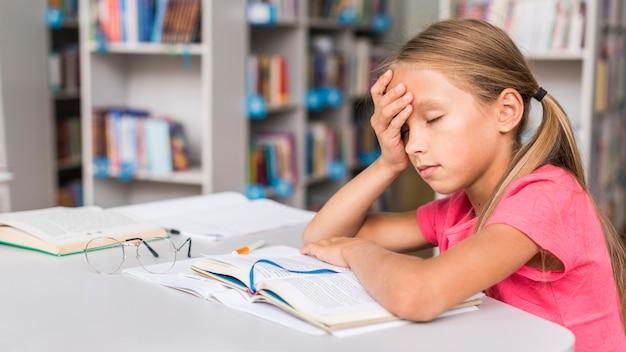 Meisje wordt moe na haar huiswerk met kopie ruimte