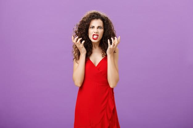 Meisje wordt pissig, ziek en moe met een irritante vrouw op een feestje die vuisten knijpt in woede en ergernis die grimassen maakt en teleurgestelde, verontruste uitdrukking praat over pijn in de kont over de paarse muur.