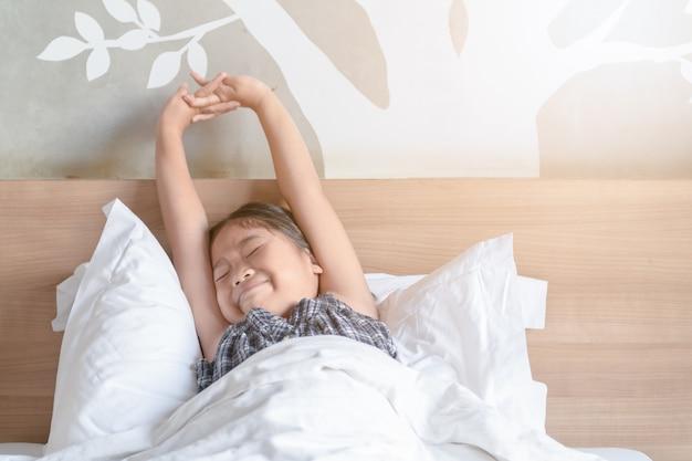 Meisje wordt wakker en strekt zich uit op bed in de ochtend,