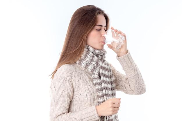 Meisje wordt ziek en drinkt pilwater geïsoleerd op een witte achtergrond