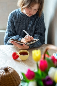 Meisje writinig in een notitieboekje, gebreid rood hart en een kopje thee op tafel. keuken
