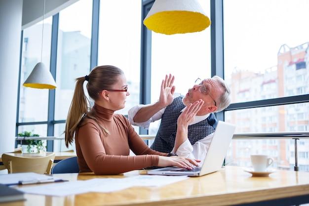 Meisje zakelijke dame zit aan een houten tafel met een laptop en bespreekt een nieuw project met haar baas mentor leraar. nieuw bedrijfsontwikkelingsconcept