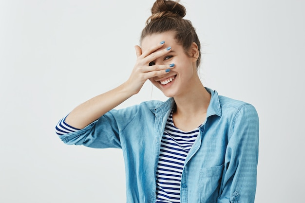 Meisje zegt domme woorden en schaamt zich. binnenschot van leuke slanke vrouw in modieus kledingstuk, die ogen behandelen met hand maar gluren, breed glimlachend, positieve emoties uitdrukken