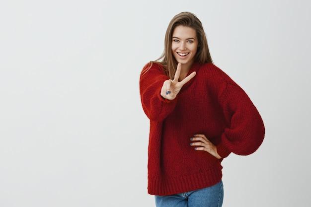 Meisje zegt hallo tegen avonturen. binnenschot van aantrekkelijk europees wijfje in trendy losse rode sweater, die overwinning of vredesteken tonen, in speelse stemming zijn, die vertrouwen uitdrukken