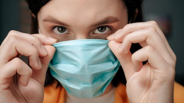 Meisje zet ademhalingsmasker op. aantrekkelijke vrouw zet op gezichtsmasker en kijkt naar de camera