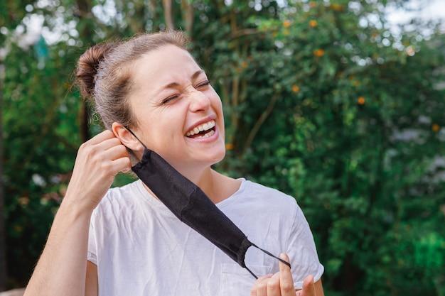 Meisje zet beschermend masker buitenshuis af jonge vrouw verwijdert masker glimlachend na vaccinatie