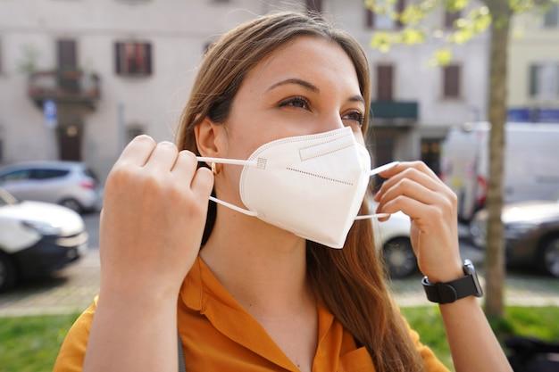 Meisje zet buiten beschermend gezichtsmasker op. close-up van een jonge vrouw met een medisch masker kn95 ffp2 in de straat van de stad.