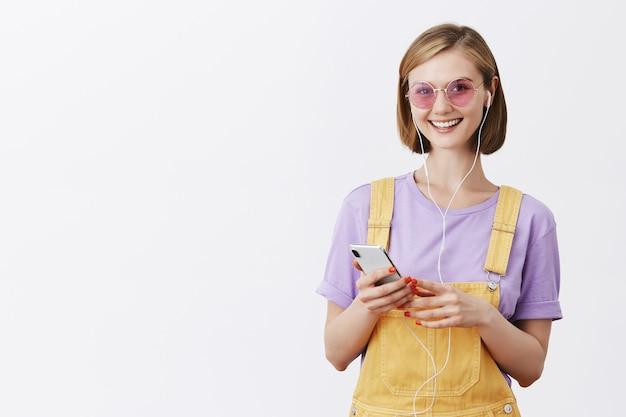 Meisje zetten oortelefoons permanent in gele tuinbroek en zonnebril, smartphone te houden en glimlachen
