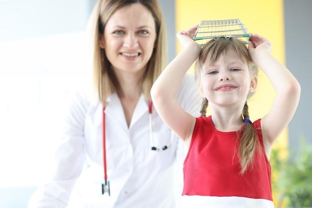 Meisje zich overgeeft aan afspraak met kinderarts in kliniek kindergeneeskunde behandeling van