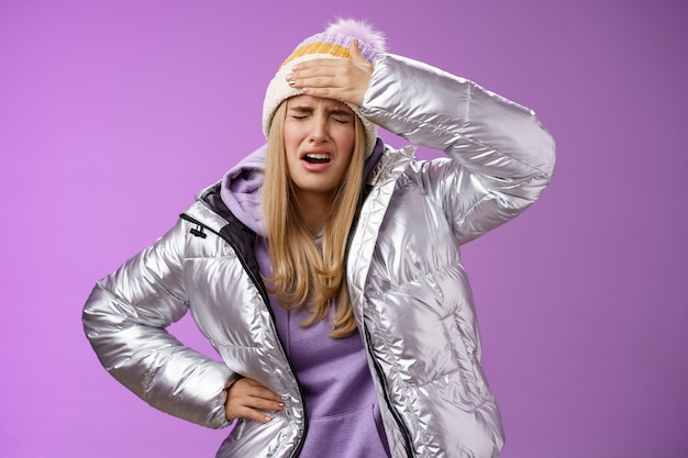 Meisje ziek moe aanraking voorhoofd pijnlijk gevoel grimassen klagen vriendje schot sneeuwbal vrouw gezicht staande gehinderd beu en boos, janken ontevreden lijden hoofdpijn, paarse achtergrond.