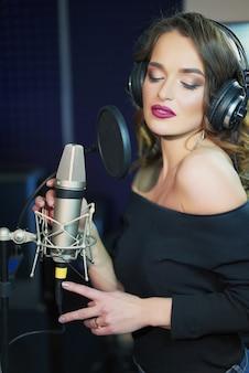 Meisje zingt naar de microfoon in een studio
