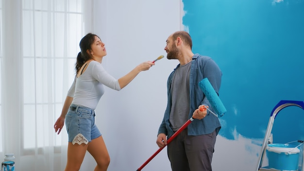 Meisje zingt op kwast en decoreert appartement met hulp van vrolijke echtgenoot. appartement herinrichting en woningbouw tijdens renovatie en verbetering. reparatie en decoreren.