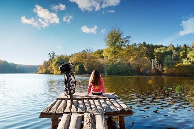 Meisje zit aan de oever van de rivier. fiets op de rivier met een tas op de kofferbak