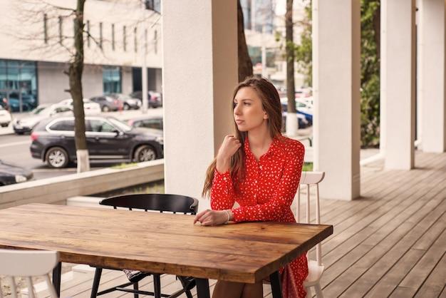 Meisje zit alleen in een café aan een tafel
