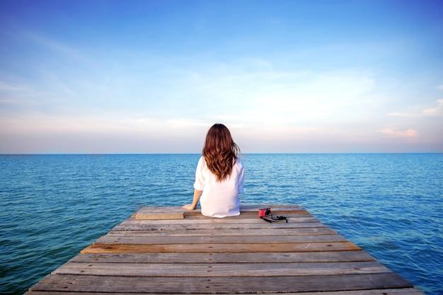 Meisje zit alleen op een de houten brug over de zee. (gefrustreerde depressie)
