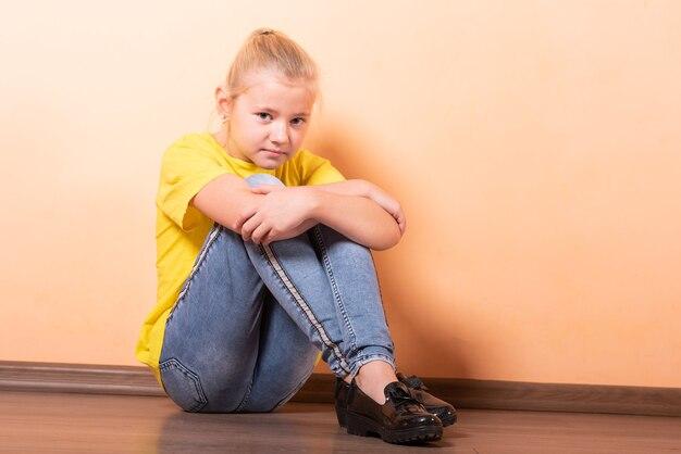 Meisje zit beledigd op de vloer, lichtoranje achtergrond. voor elk doel.