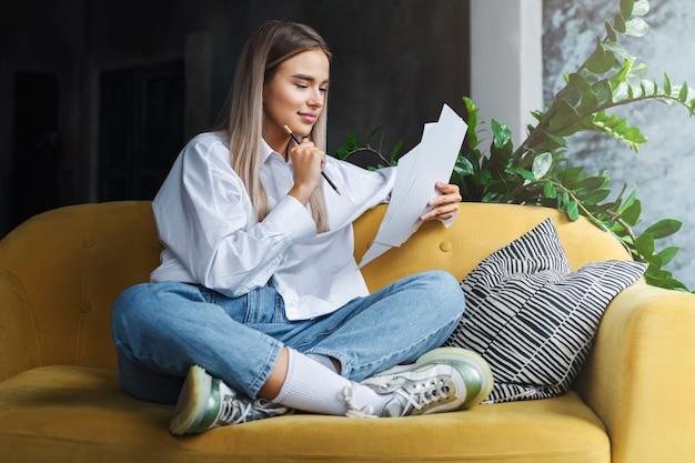 Meisje zit comfortabel thuis, ver weg werken met documenten