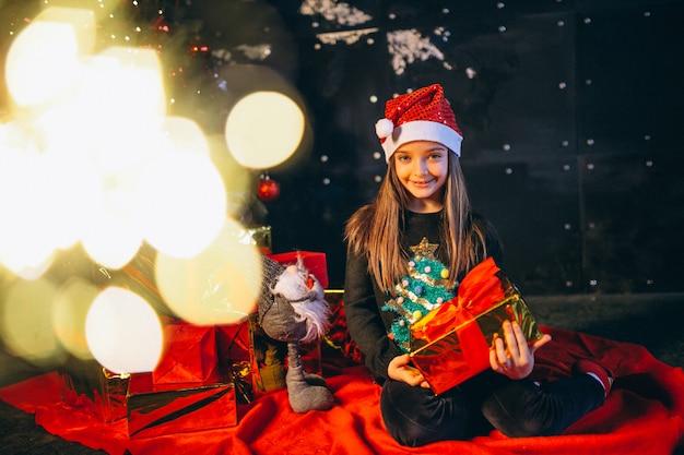 Meisje zit door kerstboom en presenteert uitpakken