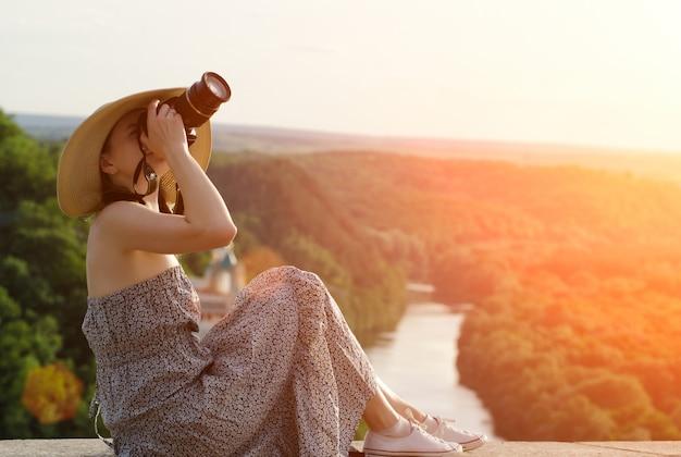 Meisje zit en neemt foto's tegen het oppervlak van bos en meanderende rivier