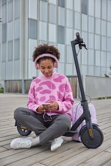 Meisje zit gekruiste benen in de buurt van elektrische scooter rust na het rijden luistert naar muziek via oortelefoons en smartphone geniet van vrije tijd in de stad surft op sociale netwerken