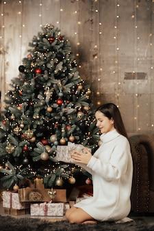 Meisje zit in de buurt van de kerstboom en houdt een kerstcadeautje.