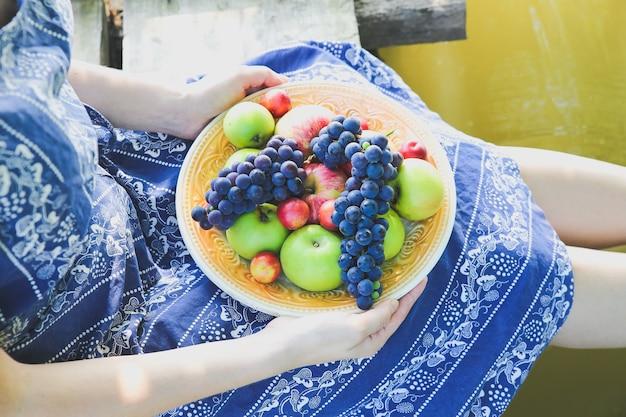 Meisje zit in de buurt van rivier in blauwe vintage jurk. vrouw houdt bord met fruit vast. rustiek zomerfruit plat gelegd. gezond vegetarisch ecologisch voedsel levensstijl concept. houten brug. zomerse sferen.