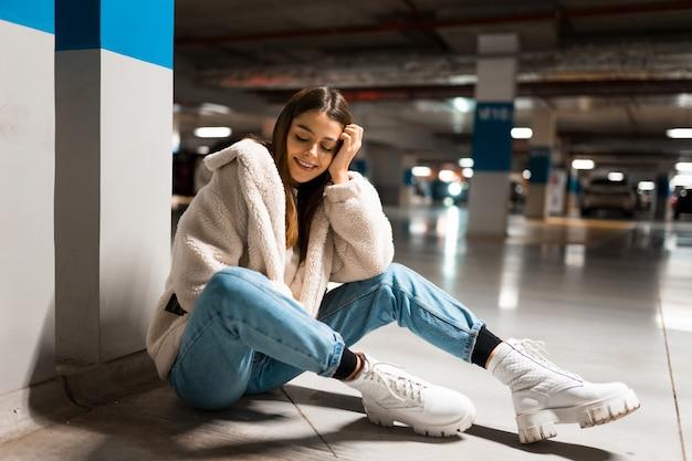 Meisje zit in de ondergrondse parkeergarage