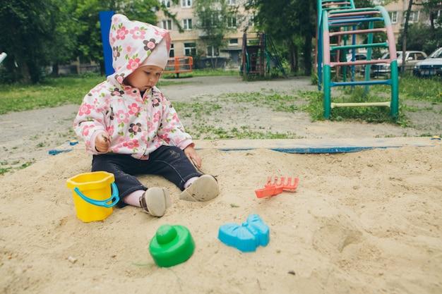 Meisje zit in de zandbak en speelt met de mal op de speelplaats klein kind speelt in het zand