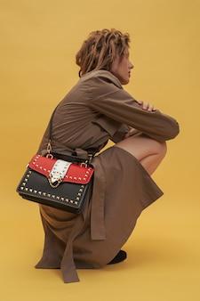 Meisje zit in een trenchcoat met een rood-zwarte tas.