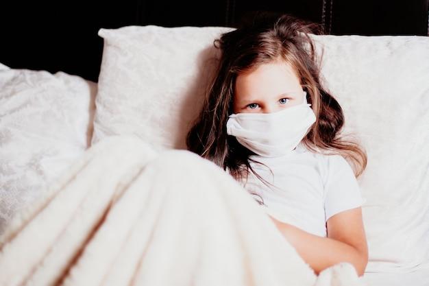 Meisje zit in een wit masker op het bed in de slaapkamer, zelfisolatie voor verkoudheid, de tweede golf van virussen.