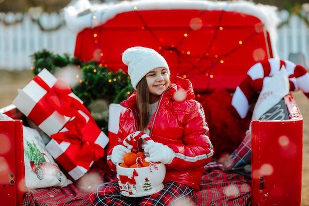 Meisje zit in rode retro auto met kerst decor en poseren met mandarijnen