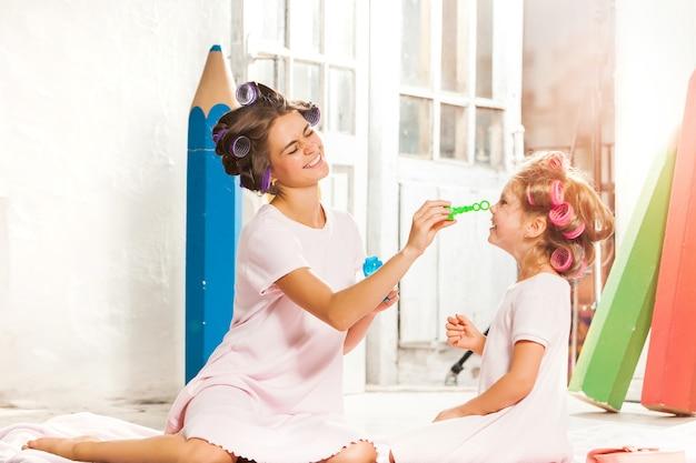 Meisje zit met haar moeder en speelt zeepbel