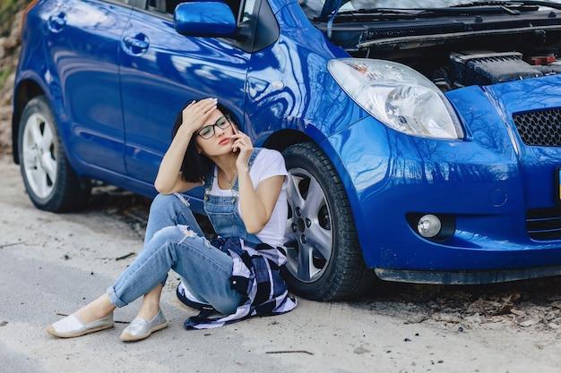 Meisje zit naast gebroken auto met een open kap en spreekt via de telefoon