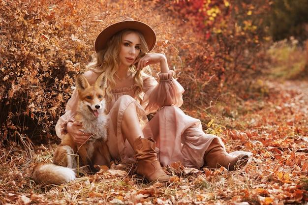 Meisje zit naast rode vos in de herfst