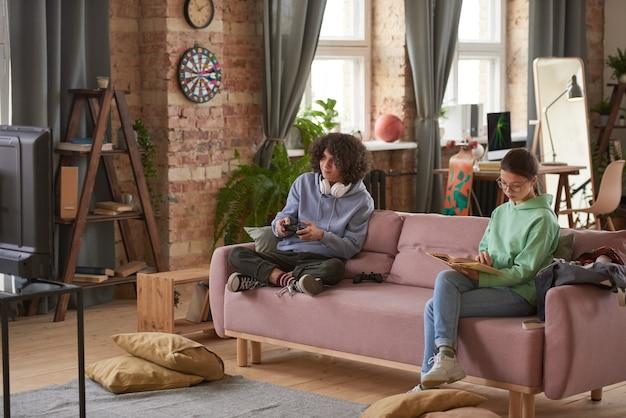 Meisje zit op de bank en leest een boek met een man die bij haar in de buurt zit en een videogame speelt in de woonkamer