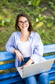Meisje zit op de bank in het park en gebruikt haar laptop